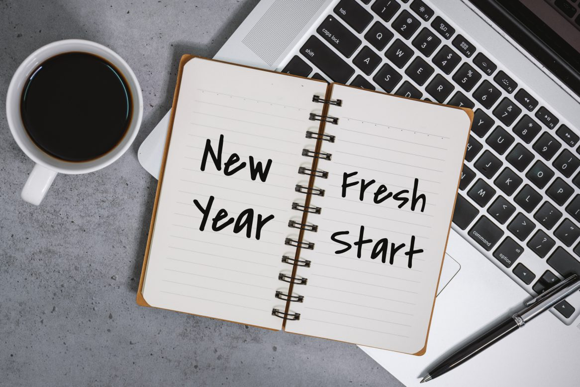 New Year Fresh Start On Notebook With Laptop Over Work Desk